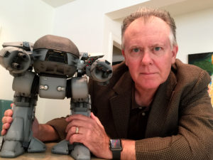"Kevin Page posses with a scale-model of the infamous ""ED-209"" from RoboCop"